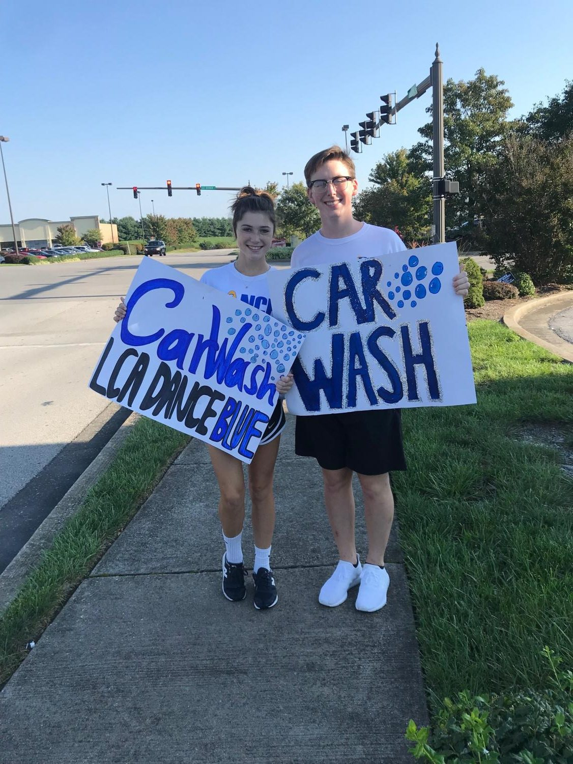 Juniors Davis McIntire and Sarah Harper advertise for the Dance Blue car wash.  The high school Dance Blue Committee is trying to raise $25,000 this year.