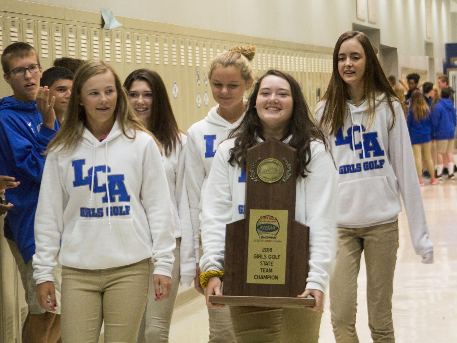 The Girls' Golf Team receives congratulations for their state championship during their Eagle Walk through the halls of the school.