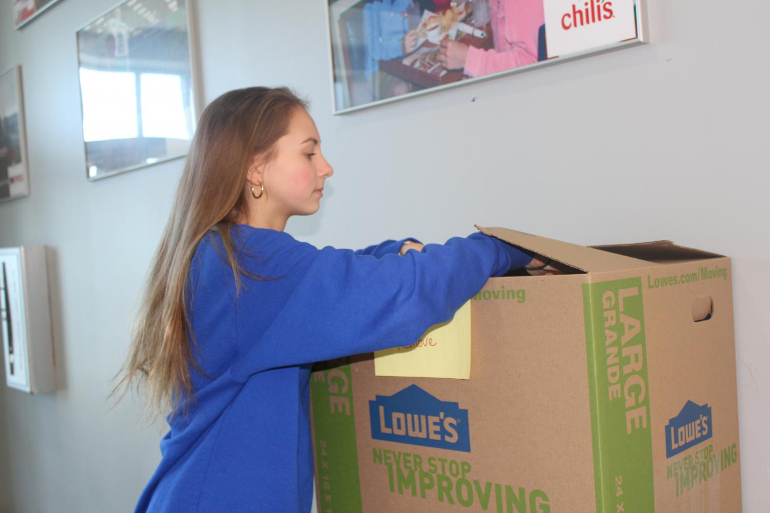 Erin Oliver, 12, adds a donation to the box for seniors.  The school is collecting hats, gloves, and socks for the Catholic Action Center who will distribute them to those in need.