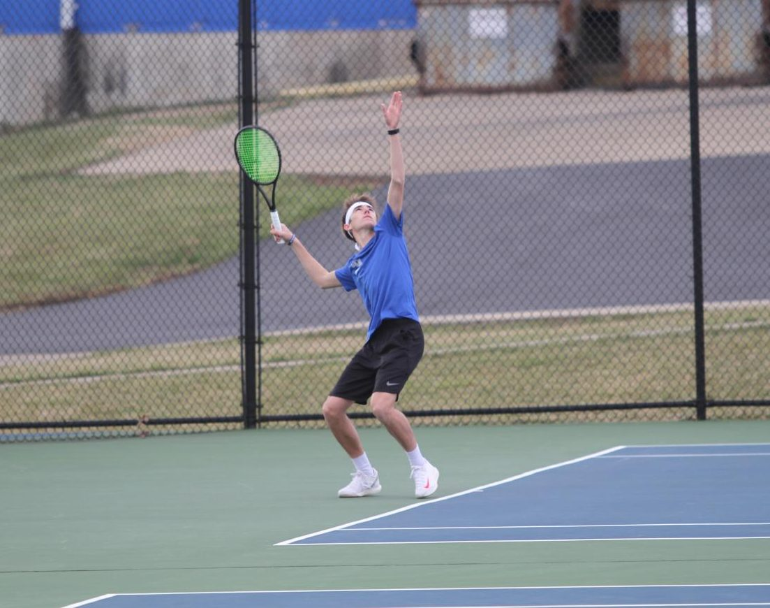 Junior Alex Horn serves in an early home match for the tennis team.