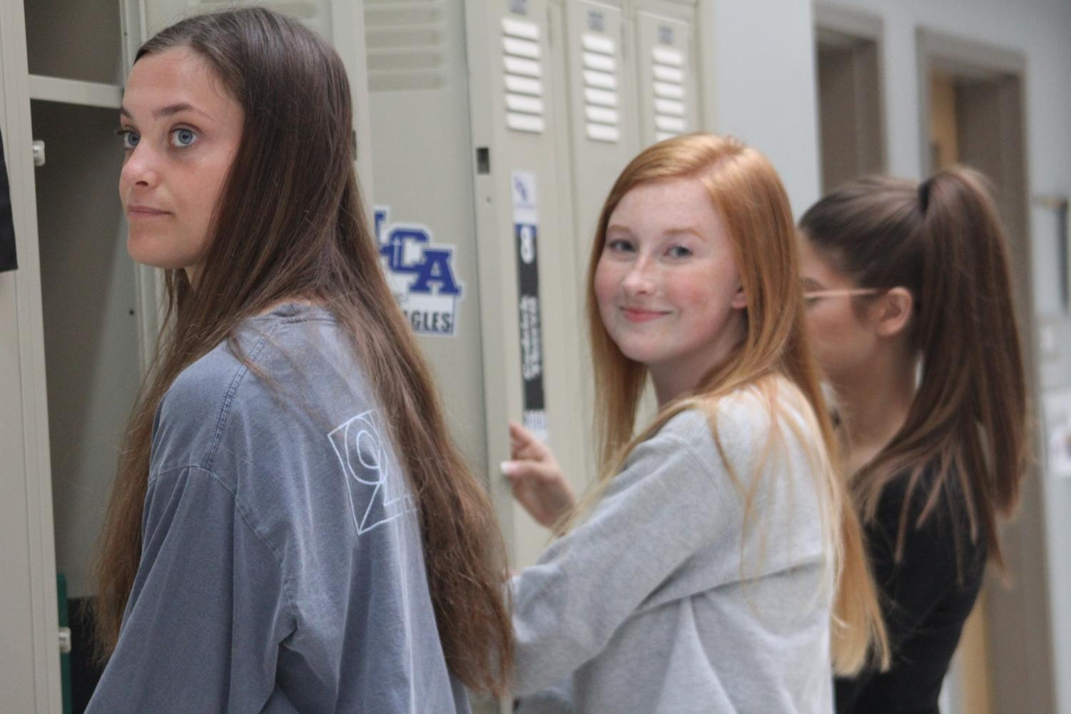 Seniors Cate Crosbie, Gretchen Casper, and Haidyn Chudy mess with the freshmen lockers as part of senior prank.