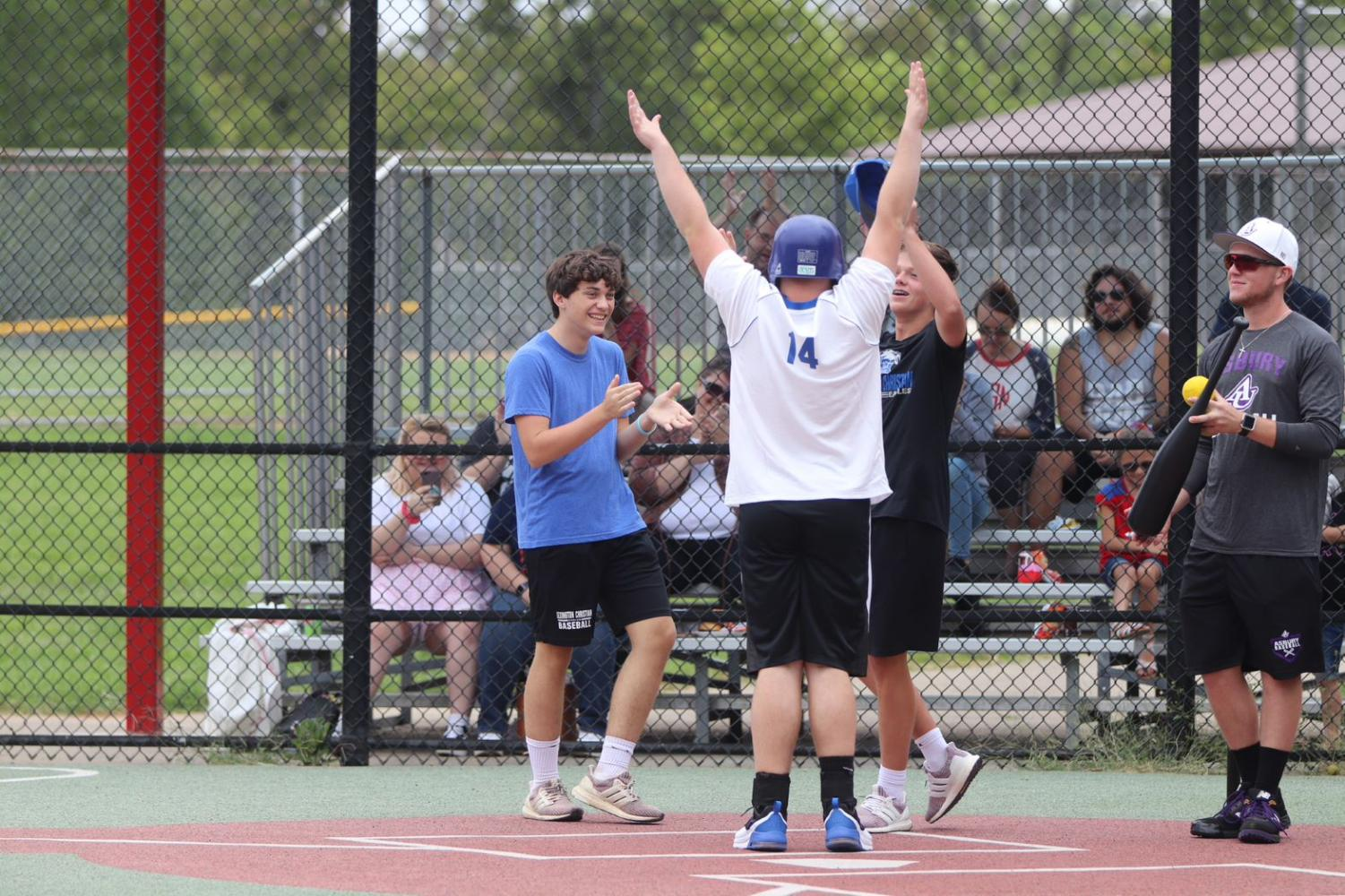 Mac Crosbie, 10, and Matthew Maggard, 10, cheer for a Miracle League player has he crosses home plate.
