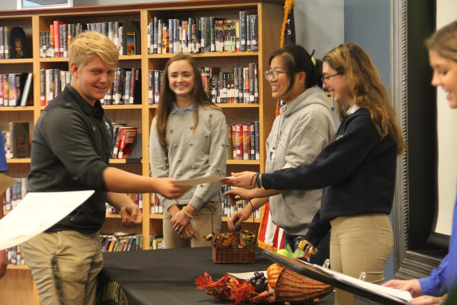 Sam Tipton, 12, receives his certificate from the Beta Club officers during the induction ceremony on Oct. 30.