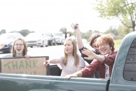 Shelby Stuary, 12, Megan Spotts, 12, Hunter Frederick, 11, and Chase Ackerman,12, greet teachers during the parade to celebrate the end of the school year for seniors.