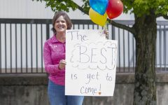 Mrs. Benson gives a colorful greeting to the seniors who drove by the school on May 12.