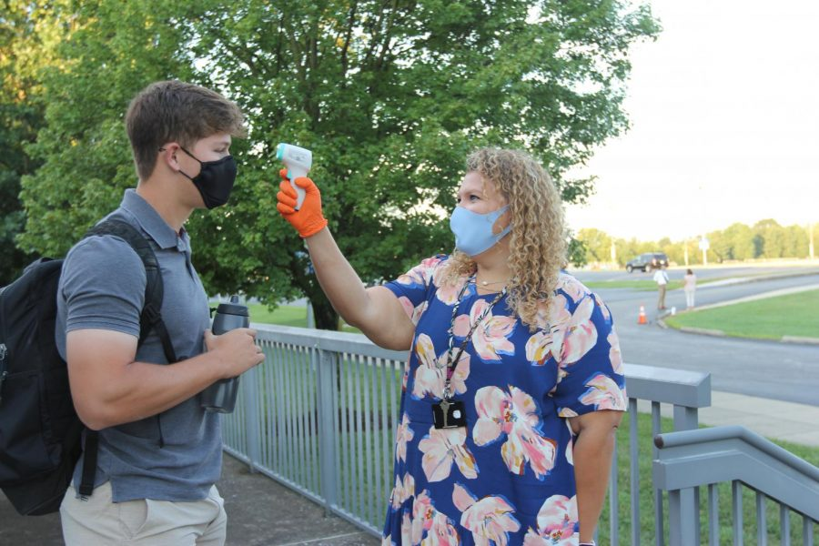 Ms. Riley takes Wyatt Guilliams, 11, temperature on the first day of school.  Temperature checks are just one of the new safety requirements in the school.