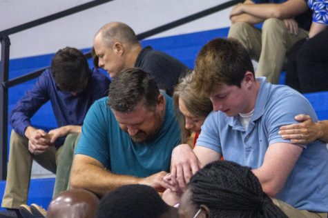 Senior Cole Ginter is surrounded by his parents as they pray over him during senior Convocation.