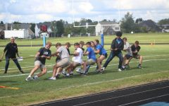 Students pull the staff over the line during the tug-of-war in the pep rally.